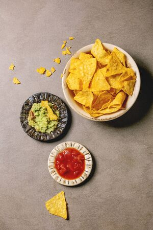 Tortilla nachos corn chips with avocado guacamole and tomato sauce served in ceramic bowl plate over brown texture background. Flat lay, space
