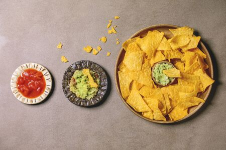 Tortilla nachos corn chips with avocado guacamole and tomato sauce served in wood plate over brown texture background. Flat lay, space