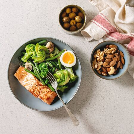 Ketogenic low carb diet dinner grilled salmon, avocado, broccoli, green bean and soft boiled egg in ceramic bowl served with olives and nuts over grey spotted background. Flat lay, space 写真素材