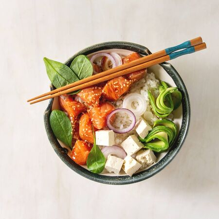 Poke bowl with soy sauce marinated salmon, rice, avocado and tofu cheese served in ceramic bowl with chopsticks over white marble background. Flat lay, space