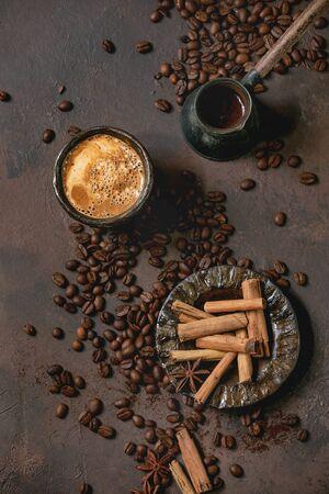 ブラックセラミックカップに泡が入ったブラックコーヒーエスプレッソ、ソーサー、セズベコーヒーポット、スパイス、ローストビーンズが茶色の