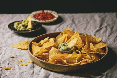 Tortilla nachos corn chips with avocado guacamole and tomato sauce served in wood plate on linen table cloth. Mexican snack 写真素材