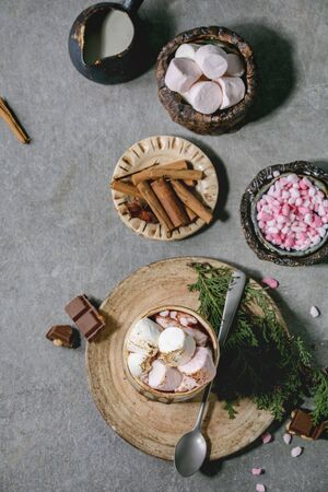 Hot chocolate or cocoa with marshmallow served in ceramic mug with saucer, cinnamon sticks, chopped chocolate, pink sugar and jug of cream over grey texture background. Flat lay, space