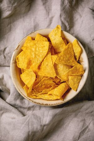 Tortilla nachos corn chips in ceramic bowl over linen folded cloth as background. Flat lay, space