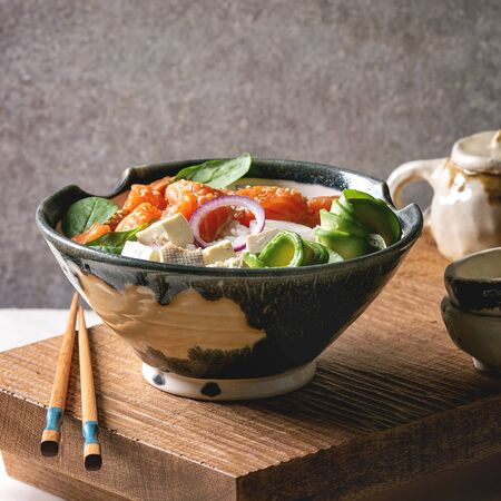 Poke bowl with soy sauce marinated salmon, rice, avocado and tofu cheese served in ceramic bowl with chopsticks and teapot on japanese wooden serving table over white marble.