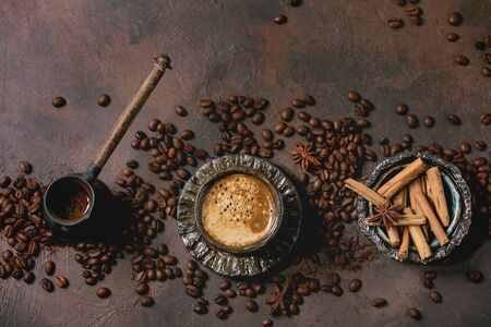 Black coffee espresso with foam in black ceramic cup, with saucer, cezve coffee pot, spices and roasted beans above over brown texture background. Flat lay, space