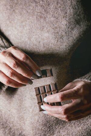 Woman beige sweater hold in hands broken dark chocolate bar