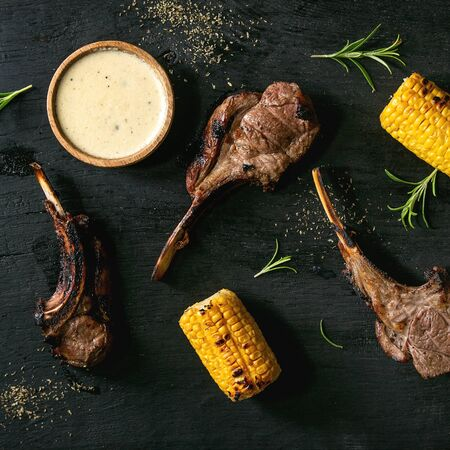 Grilled bbq rack of lamb with sweet corn cobs, rosemary and cheese sauce over black burned wooden background. Flat lay, space