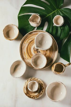 Variety of empty different ceramic dishes, bowls, jugs and plates on exotic monstera leaves over white marble background. Flat lay, space
