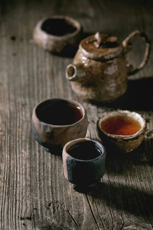 Hot black tea in different traditional wabi sabi style fireclay ceramic craft cups served with plate, teapot and bowl of dry tea leaves on old wooden table. Dark rustic atmosphere. Stock Photo