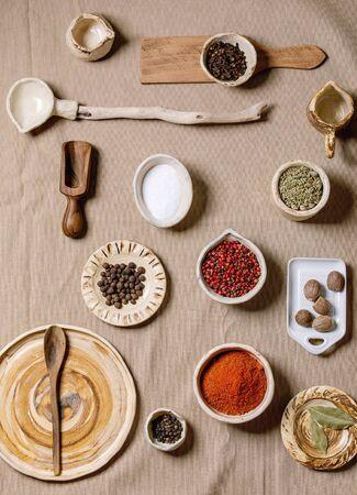 Variedad de diferentes platos de cerámica y madera hechos a mano, cuencos y cubiertos con condimentos y especias sobre tela de lino gris como fondo. Lay Flat, espacio. Concepto de cocina de cocina