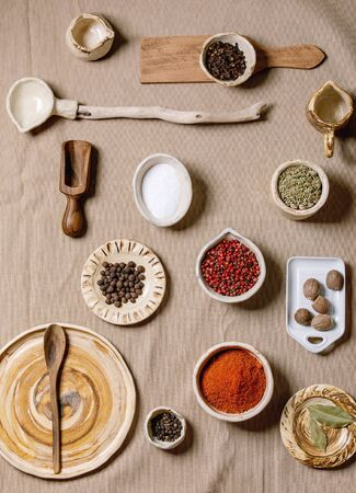 Variety of different handmade wooden and ceramic dishes, bowls and cutlery with seasonings and spices over grey linen cloth as background. Flat lay, space. Kitchen cooking concept