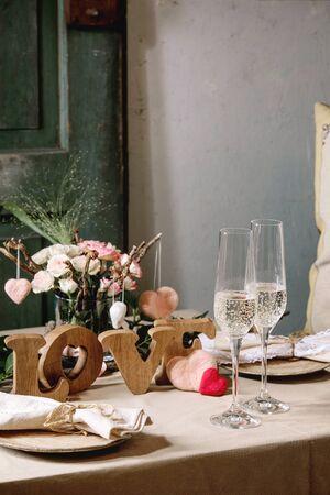 st. Cadre de table romantique pour la Saint-Valentin ou le mariage avec des lettres en bois d'amour, des coeurs feutrés à l'aiguille, des assiettes en céramique, un bouquet de roses roses, quelques verres de champagne sur une nappe en lin naturel.