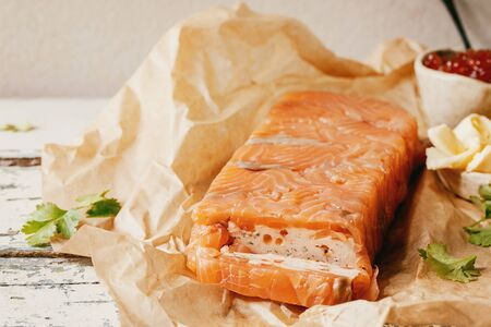 Red salmon caviar in ceramic bowl and homemade salmon terrine served with butter on crumpled paper over old wooden table. Rustic style Stok Fotoğraf - 137888852