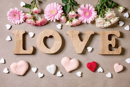 Word LOVE from oak wooden letters with variety of pink roses flowers and felted hearts over brown texture background. Flat lay, space. St. Valentines romantic greeting card Foto de archivo - 137887612