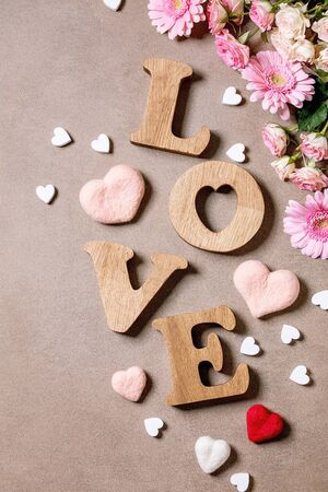 Word LOVE from oak wooden letters with variety of pink roses flowers and felted hearts over brown texture background. Flat lay, space. St. Valentines greeting card Foto de archivo - 137887945