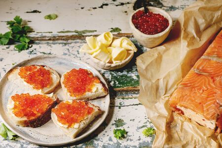 Red salmon caviar in bowl and on wheat bread, homemade salmon terrine served with butter on ceramic plate over old wooden table. Rustic style Stok Fotoğraf - 137887365