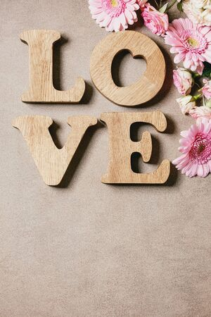 Word LOVE from oak wooden letters with variety of pink roses flowers over brown texture background. Flat lay, space. St. Valentines greeting card Foto de archivo - 137887408