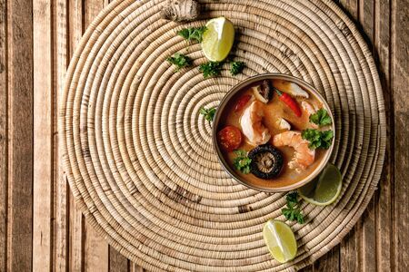 Traditional spicy Thai soup tom yum kung with shiitake mushrooms and prawns, ingredients above on straw wicker napkin over wooden plank background. Flat lay, space