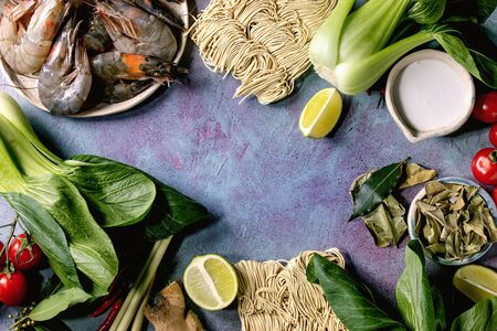 Raw prawns shrimp with asian noodles, cocnut milk and vegetables. Ingredients for cooking asian dinner or thai soup tom yum. Blue concrete background. Flat lay, space