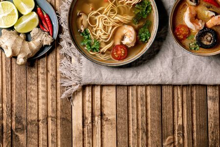 Variety of asian soups. Traditional spicy Thai tom yum kung and noodles soup with shiitake mushrooms, prawns, ingredients above on linen cloth over wooden plank background. Flat lay, space.