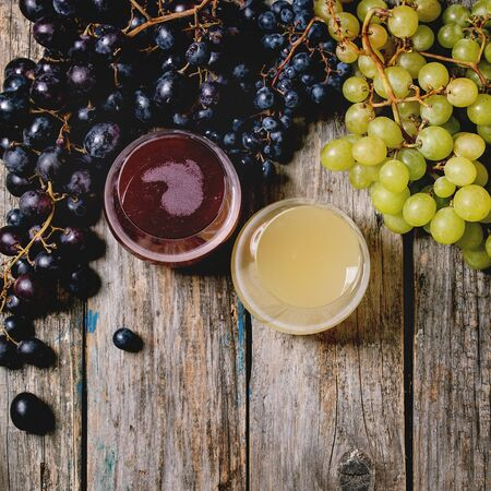 Traditional New european low alcohol red and white wine Federweisser or Neuer Wein, Burcak, Vin bourru in glasses with black and green grapes bunches over old wooden background. Flat lay, space Reklamní fotografie