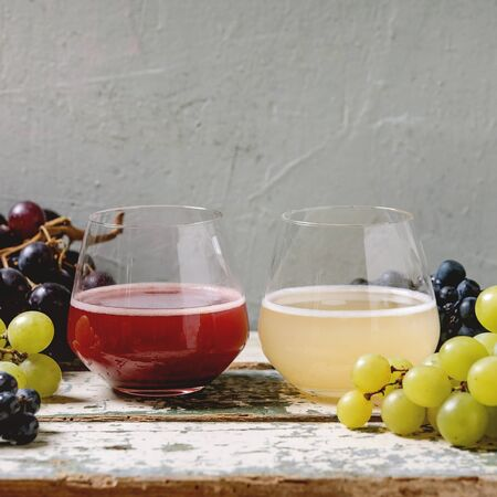 Traditional New european low alcohol red and white wine Federweisser or Neuer Wein, Burcak, Vin bourru in glasses with black and green grapes bunches on old white wooden table. Copy space.