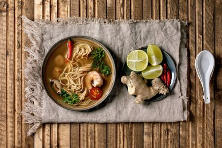 Traditional spicy Thai soup tom yum kung with shiitake mushrooms and prawns, ingredients in plate, spoon on linen cloth over wooden plank background. Flat lay, space. Asian style dinner 写真素材