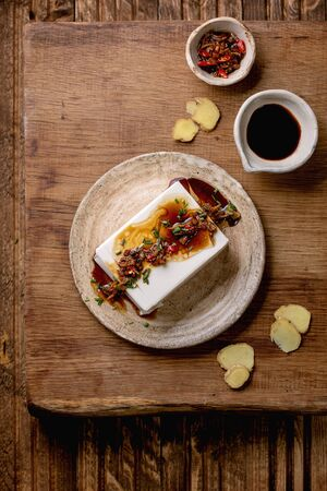 Silk tofu japanese soy cheese whole piece with chili ginger, chive and soy sauce topping on ceramic plate over wooden table. Flat lay, space