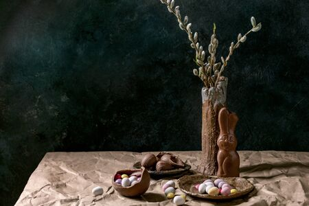 Easter mood still life with blossom willow branches in ceramic vase, traditional chocolate rabbit, eggs and sweets on table with crumpled craft paper. Dark background.
