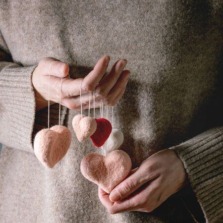 Woman in cashmere sweater hold in hands variety of needle felted hearts on threads. St Valentines day greeting card 版權商用圖片