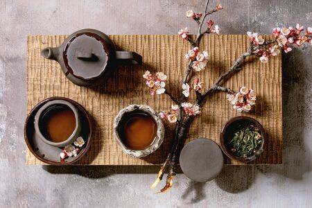 Tea drinking wabi sabi japanese style dark clay cups and teapot on wooden tea table with blooming cherry branches. Grey texture concrete background. Flat lay, space