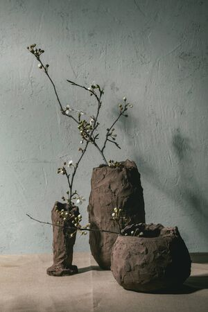 Blossom cherry branches in different craft clay vases on grey table cloth. Spring interior decorations. 版權商用圖片
