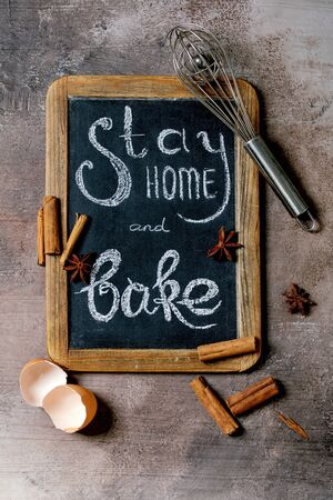 Ingredients and tools for baking. Stay home quarantine isolation period concept. Vintage chalkboard with handwritten chalk lettering Stay home and bake. Grey texture background. Flat lay, space Фото со стока