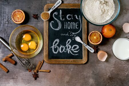 Ingredients for baking. Stay home quarantine isolation period concept. Vintage chalkboard with handwritten chalk lettering Stay home and bake. Grey texture background. Flat lay, space