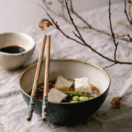 Japanese Miso broth soup with silk tofu cubes, soy beans edamame, green beans in ceramic bowl with chopsticks on grey linen table cloth with autumn branches. Asian dinner.