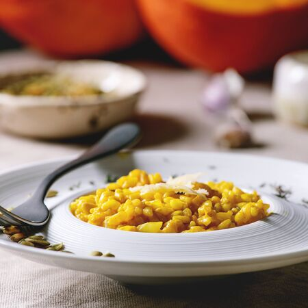 Traditional vegetarian pumpkin risotto italian dish in ceramic plate on linen table cloth with ingredients above. Dark rustic style
