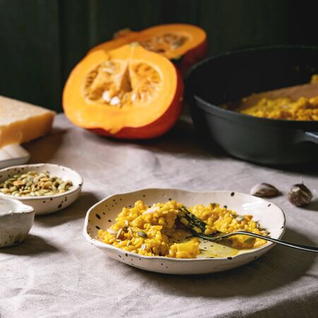Eaten Traditional vegetarian pumpkin risotto italian dish in ceramic plate on linen table cloth with ingredients above. Dark rustic style
