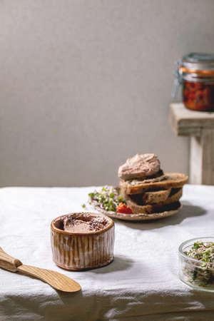 Ceramic bowl of homemade chicken liver pate with wooden knife, sliced rye bread, sun-dried tomatoes and green sprout salad on white linen table cloth. Home breakfast or appetizer 版權商用圖片 - 151055364