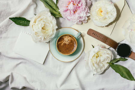 Cup of espresso coffee, blank paper, envelope, smart watch, pink and white peonies flowers with leaves over white cotton textile background. Flat lay, copy space 版權商用圖片 - 150758747