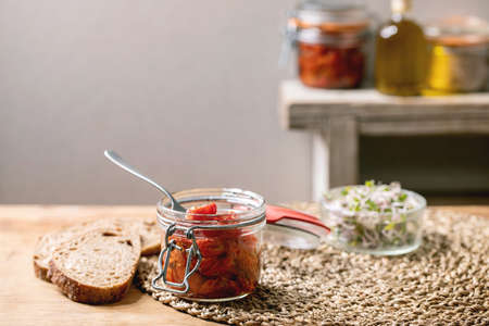 Sun-dried cherry tomatoes olive oil in glass jar with fork, standing on wooden kitchen table with sliced rye bread and green sprouts salad. 版權商用圖片