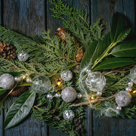 Green Christmas table decor thuja branches, leaves, silver balls and lighted garlands over dark blue wooden background. Flat lay, space. Christmas and New year decorations or greeting card.