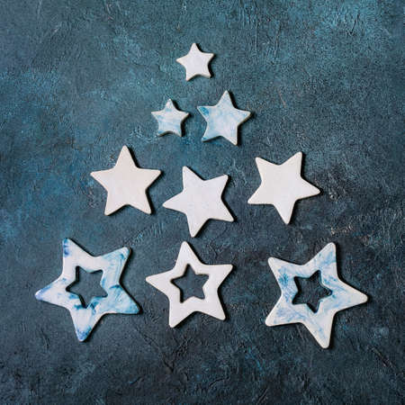 Christmas decoration ceramic stars white and blue glazed, different size, as christmas tree shape over blue texture background. Christmas and New year greeting card. Flat lay, space.
