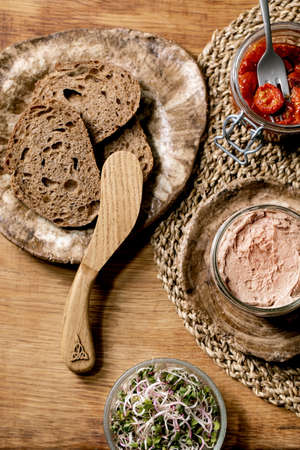 Glass jar of homemade chicken liver pate with wooden knife, sliced rye bread, sun-dried tomatoes and green sprout salad on wooden background. Home breakfast or appetizer. Flat lay