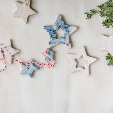 Christmas decoration ceramic stars white and blue glazed, different size, green branches over white marble background. Christmas and New year greeting card. Flat lay, copy space.
