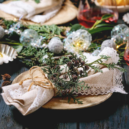 Christmas or New year table setting with empty ceramic plates, wine glasses, napkins, Christmas thuja wreath, luminous garland and burning candles on dark wooden plank table. Holiday mood