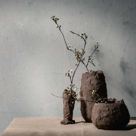 Blossom cherry branches in different craft clay vases on grey table cloth. Spring interior decorations.