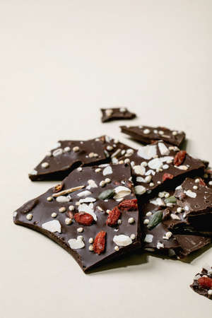Handmade chopped dark chocolate with different superfood additives seeds and goji berries over beige background. 版權商用圖片 - 151508864