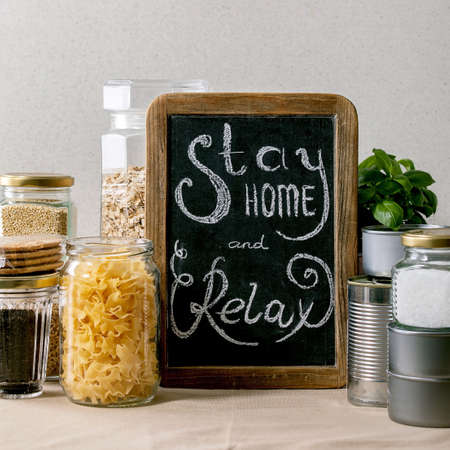 Food supplies crisis food stock for quarantine isolation period. Different glass jars with grains, pasta, cans of canned food, toilet paper, chalkboard handwritten chalk lettering Stay home and relax.