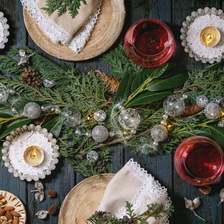 Christmas or New year table setting with empty ceramic plates, wine glasses, napkins, Christmas thuja wreath, luminous garland and burning candles on dark wooden plank table. Holiday mood flat lay 版權商用圖片 - 151509117